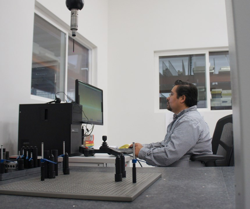 A measuring probe protrudes downward toward the table of a coordinate measuring machine, while an employee sits at a computer in the background.