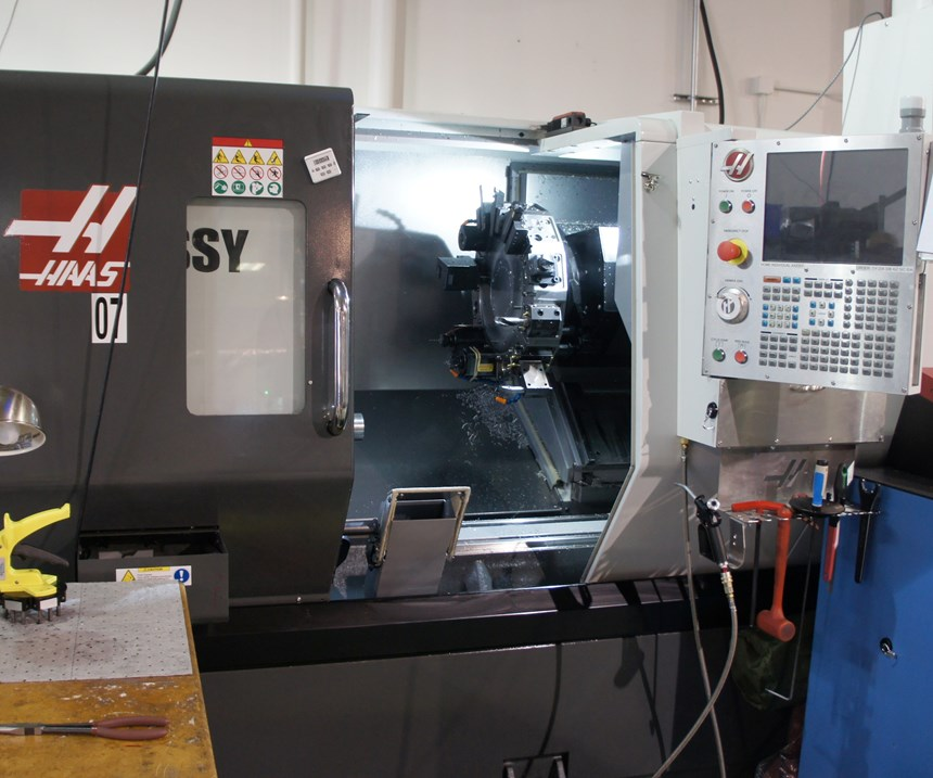 A lathe with the door open to reveal a tool turret and chips left over from the previous custom machining work