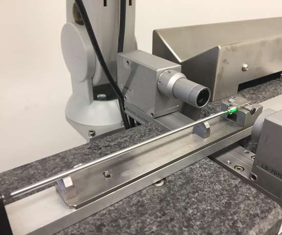 A part slides by the P4K laser scanner on a moving stage after grinding. This automated inspection device offers the capability to measure every part, analyze the data and issue dressing program corrections back to the CNC.