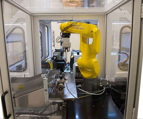 A 6-axis Fanuc LR Mate robot transfers parts from feeder to grinder and from grinder to P4K laser inspection.