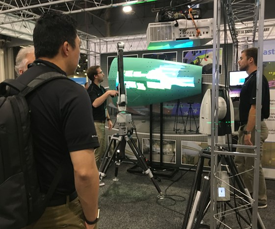 A HxGN Live 2018, attendees look on as a company representative uses a scanner to capture the geometry of a large aircraft wing structure.