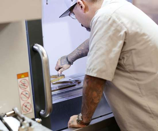 Trainees like John Villa at Rise Up Industries learn basic skills in CNC machine operation.