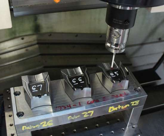 A measuring probe conducts an in-process inspection within the workzone of a vertical machining center.