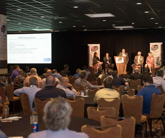 Attendees to the most recent top shops conference listen to a panel discussion about strategies empoeyd by leading shops.