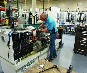 Anthony Staub works a manual lathe at Staub Machine