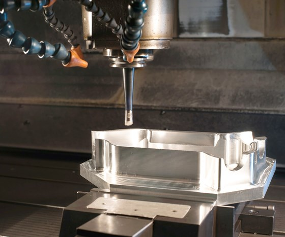 A three-axis end mill approaches a mold cavity for a machining operation within the workzone of a three-axis vertical machining center.