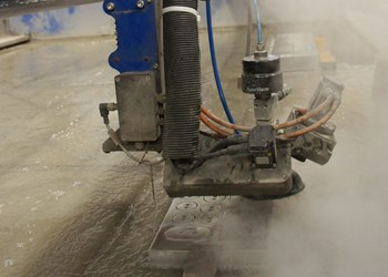 International Mold Corporation's waterjet goes to work on a set of shims. Since installation three years ago, the machine has been employed for manifolds, ejector plates, wear plates, gibs, fixtures and various other parts.