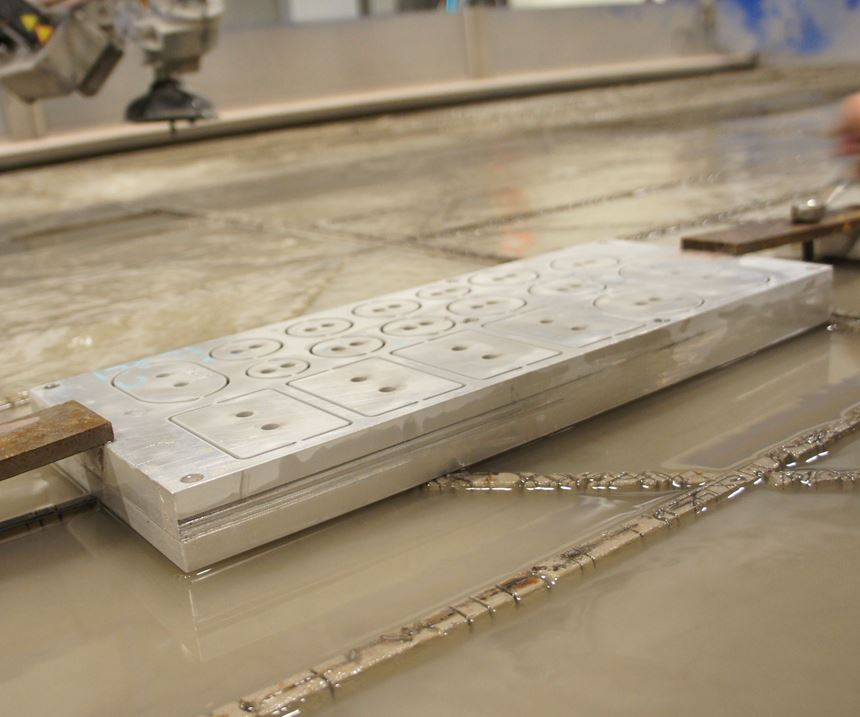 Mounting a stack of shims to the waterjet table between two aluminum plates enables cutting all the geometry at once.
