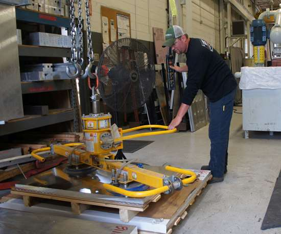 Aaron Bazydlo, primary operator of the waterjet, uses a vacuum loader to set up large plates for cutting.