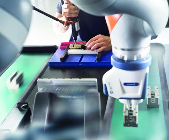 A human and a cobot with a Schunk Co-act gripper working in close proximity