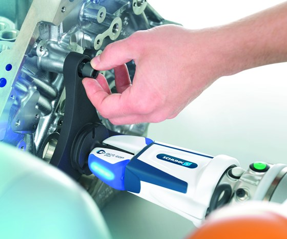 A cobot with a Schunk Co-act gripper holds a part in place while a person assembles it