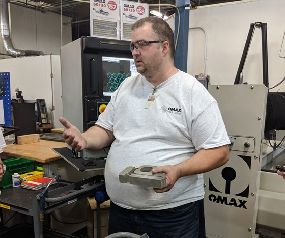 Omax employee holding a waterjet component