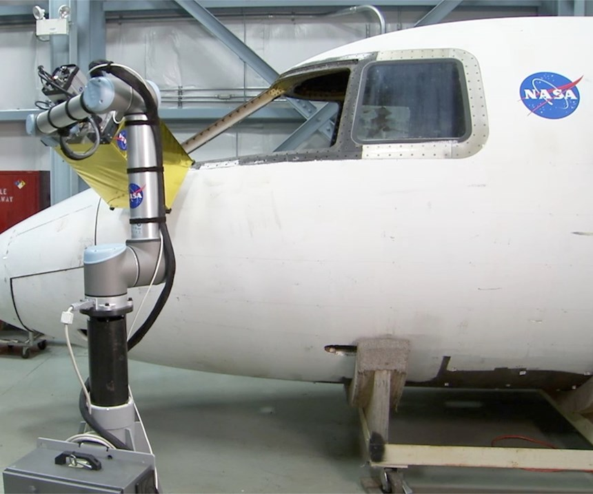 A Universal Robots collaborative robot performing an infrared inspection program on an airplane fuselage