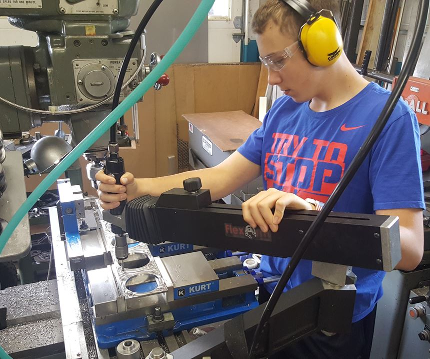 Shop owner Rob Little's 13-year-old son taps holes on a component with the FlexArm