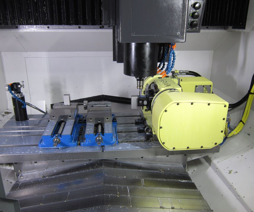 A Renishaw tool breakage detection system, two vises and a rotary table inside a machine