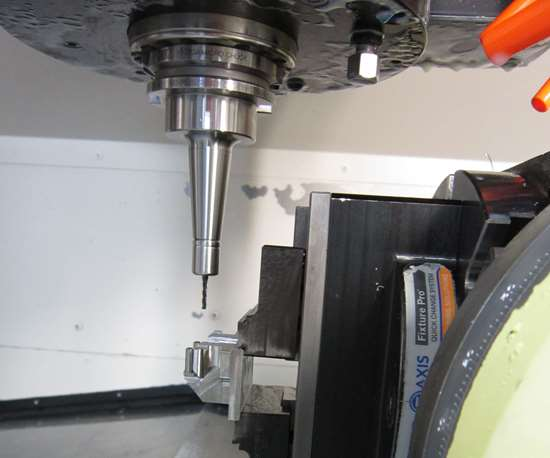 A long toolholder with a cutting tool and a part on a rotary table inside a machine