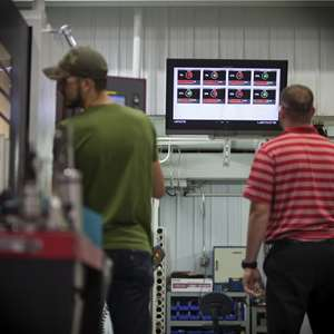 Personnel view machine utilization information on a monitor overlooking the floor of a machine shop..