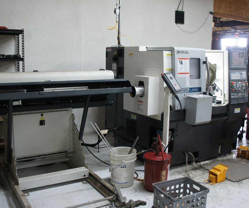 An Okuma Genos L250 lathe is equipped with a barfeeder for unattended operation.