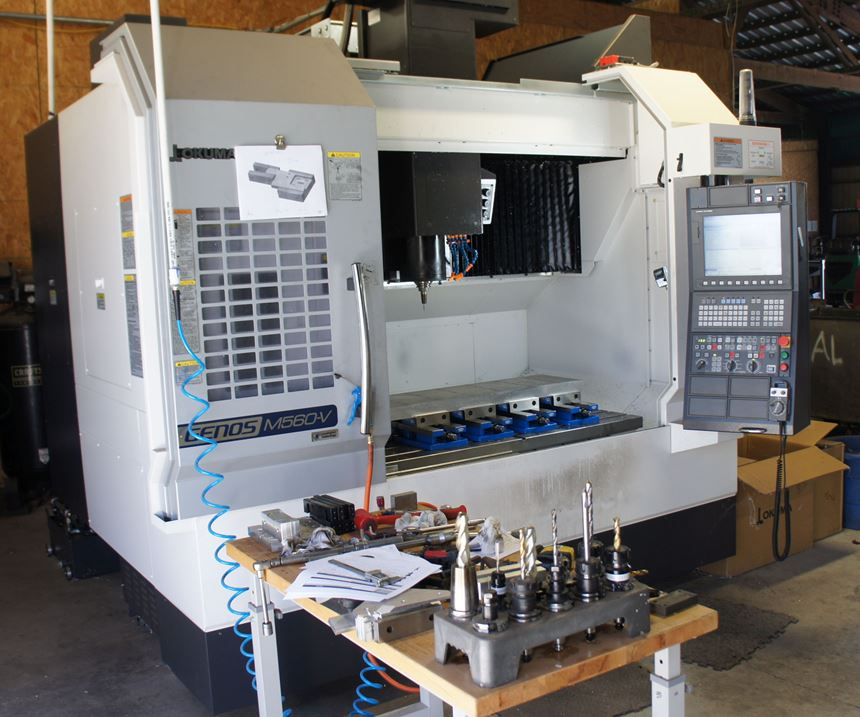 Wenteq's Okuma three-axis vertical machining center with the door open, set up and ready to machine.