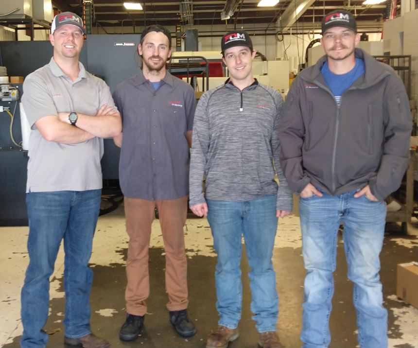 four men standing in a machine shop