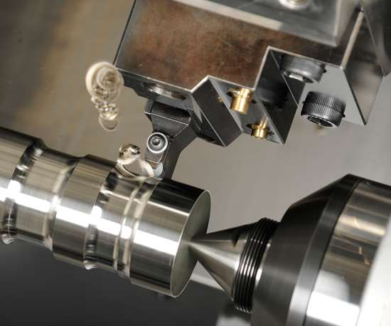 Chips curl off a shaft as a ceramic cutting tool insert takes a profile cut on a CNC turning machine.