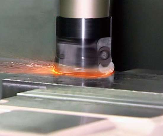 Fire spits from the workzone of a CNC machining center during a milling routine with ceramic cutting tool inserts .