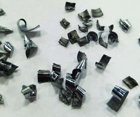 A pile of short, curlicue-shaped chips generated by a properly performing, replaceable-tip drill in a deep-hole CNC machining application.