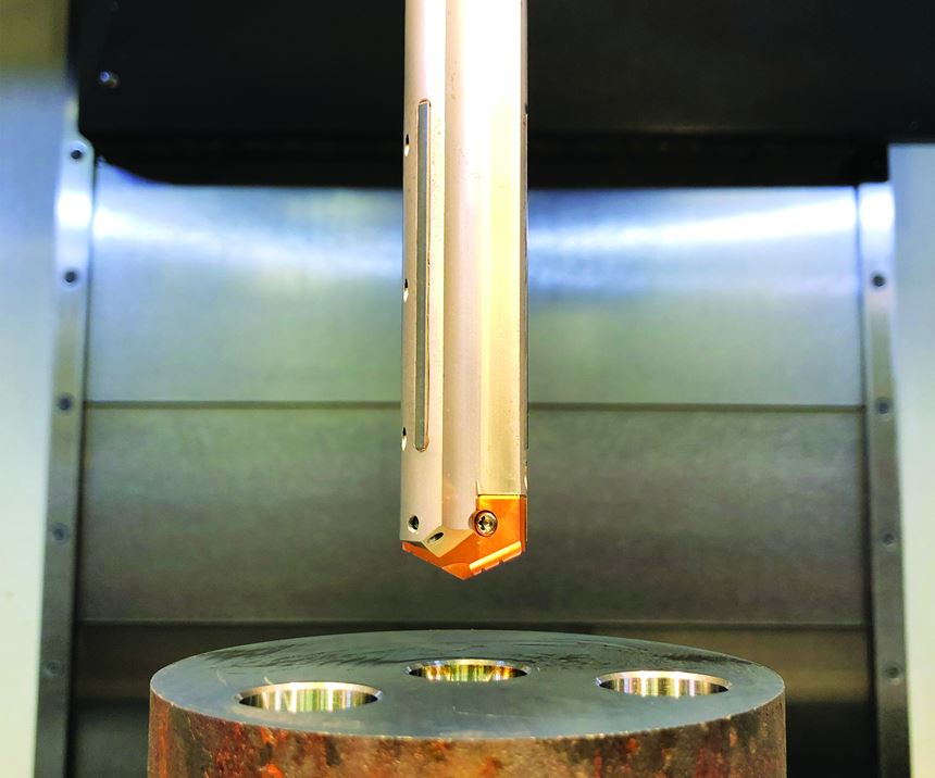Depicted hovering over a workpiece, Allied Machine & Engineering's Stealth Drill features carbide guiding pads, extra through-coolant orifices and an adjustable locating pin that moves the insert radially to mitigate the stack-up of tolerances common to all replaceable-tip drills.