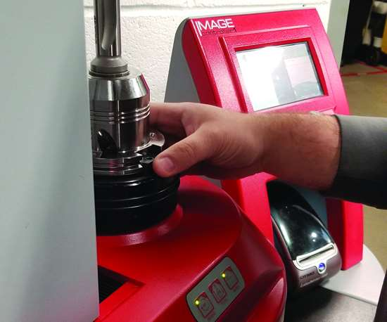 A person adjusts a drilling tool assembly on a digital presetter.