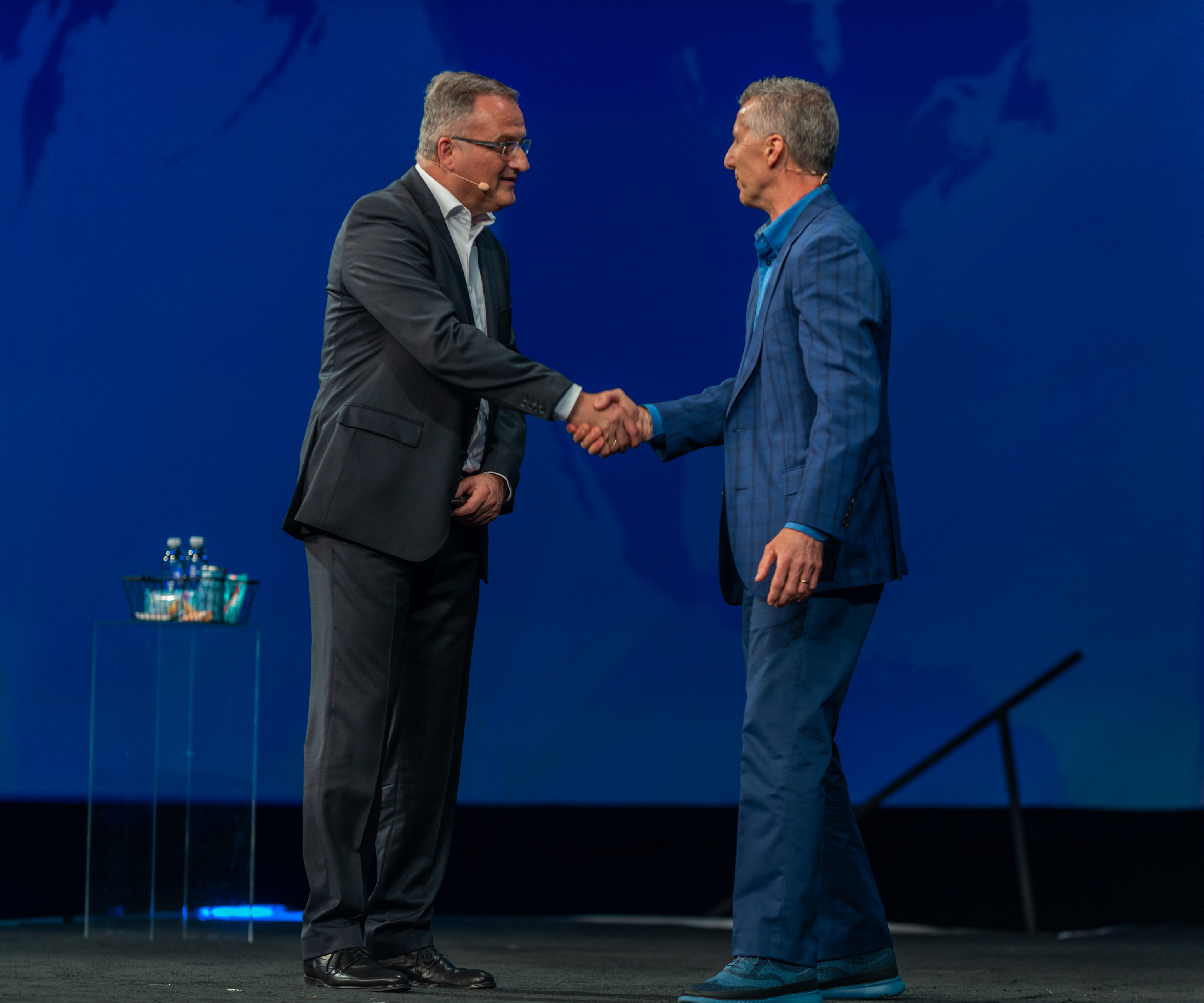 Speaking at HxGN Live, Hexagon's annual conference in Las Vegas, Norbert Hanke, president of Hexagon Manufacturing Intelligence, greets guest speaker Doug Woods, president of AMT-The Association for Manufacturing Technology. (Photo courtesy of Hexagon).