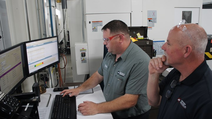 Director of business operations Patrick Boyle looks on as milling team leader Tim Rutkowski reviews current priorities and how priorities will shift based on changing threat levels.