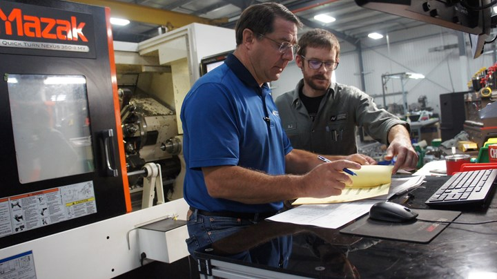 People consult on the shop floor at CNC machine shop Northwood Industries (NWI).