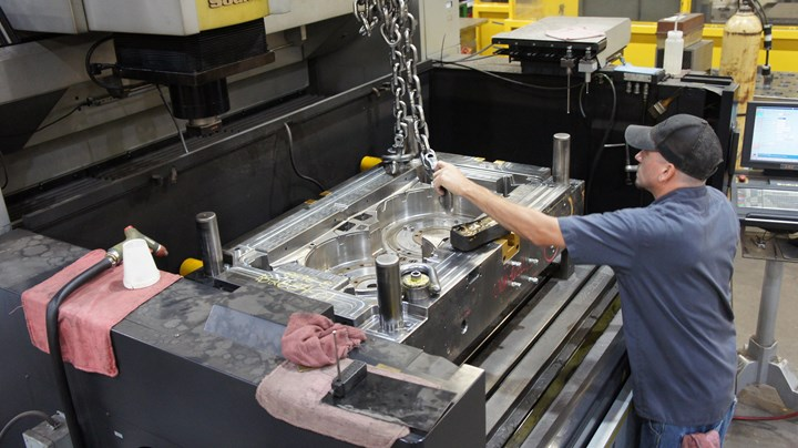 An employee at plastic injection mold manufacturing and CNC machining operation B & J Specialty loads a mold into a large machining center.