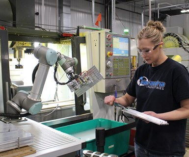 manufacturing employee works with collaborative robot