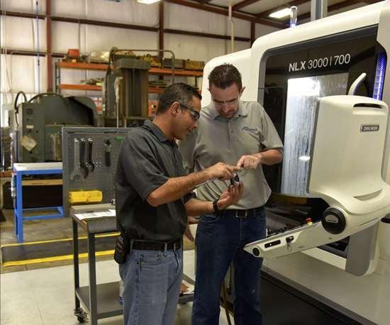 El gerente de operaciones, Mohsen Saleh, (a la izquierda) y el operario de máquinas CNC, Mark Garland, (a la derecha) discuten sobre una pieza de trabajo producida en uno de los centros de torneado universales DMG MORI NLX 3000 | 1250 de Anthony Machine.