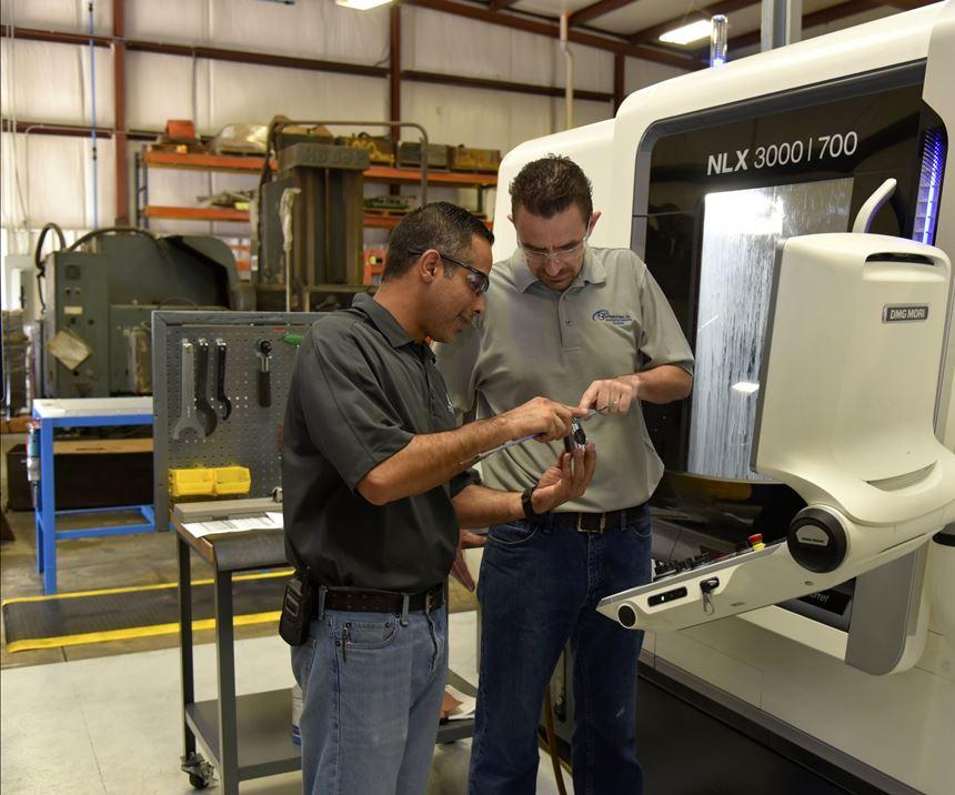 El gerente de operaciones, Mohsen Saleh, (a la izquierda) y el operario de máquinas CNC, Mark Garland, (a la derecha) discuten sobre una pieza de trabajo producida en uno de los centros de torneado universales DMG MORI NLX 3000   1250 de Anthony Machine.