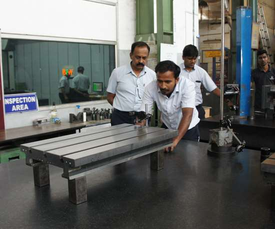 Employees measure a component at a BFW machine tool manufacturing facility.
