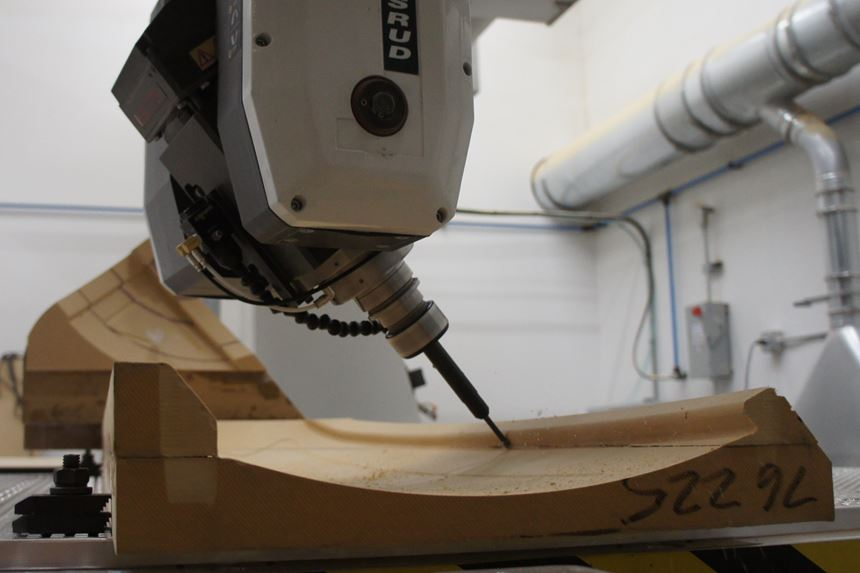 A close-up of a tool on a five-axis spindle machining a medium-density fiberboard vacuum workholding fixture.