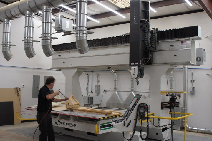 At DeltaWing, large blowers direct waste material into collection units behind a large Onsrud five-axis  machine.
