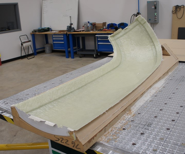 This fiberglass part is a body panel for Ollie, the autonomous bus developed by Local Motors, for trimming operations. Large, thin, contoured workpieces like this are common among the shop's aerospace work.