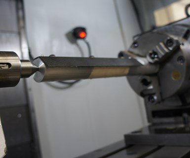 A composite rifle heat shield undergoes operations on a four-axis VMC at composites manufacturer DeltaWing.