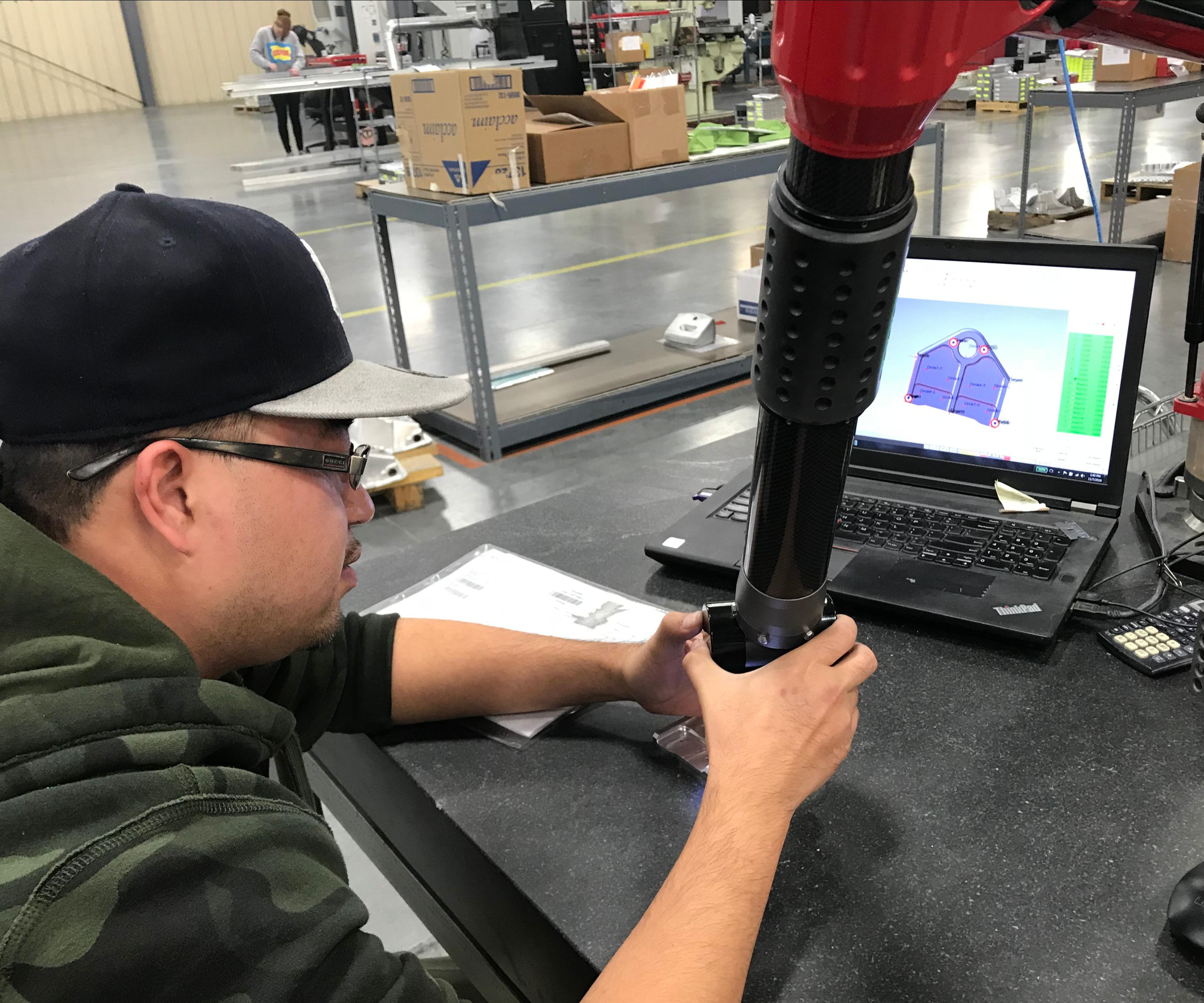 inspector handling a Romer portable arm CMM