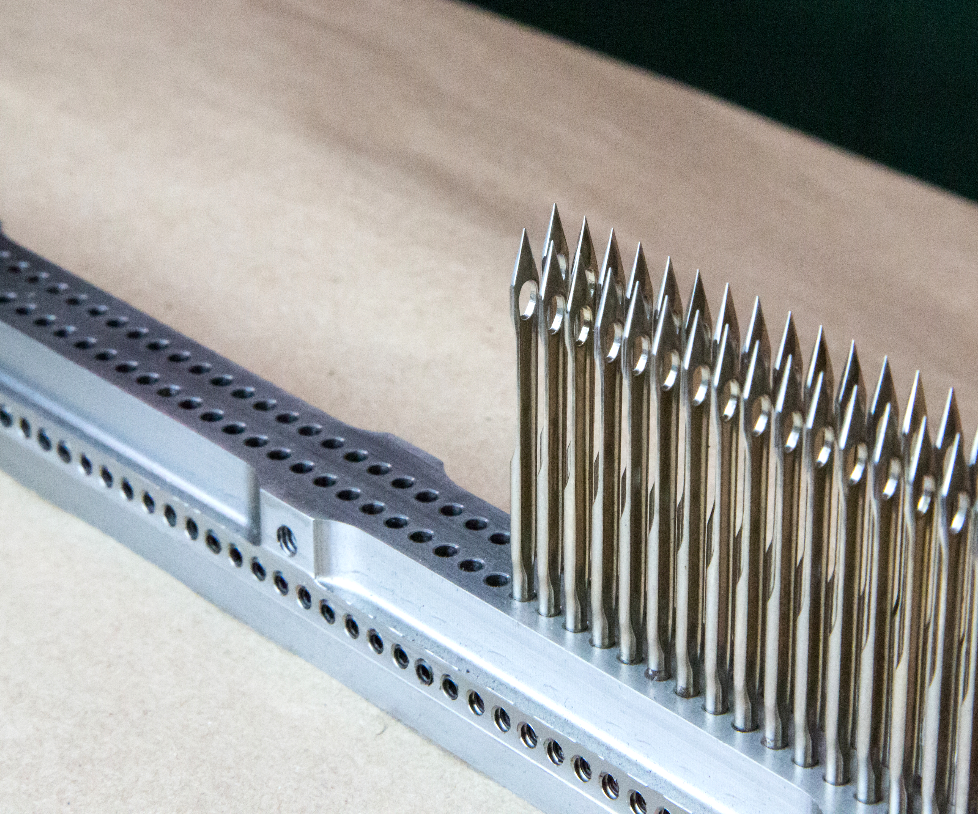 needle bar with drilled holes and tufting needles
