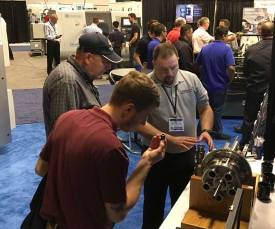 man inspects precision turned part during PMTS trade show