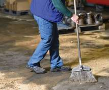 man sweeping machine shop with a broom