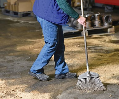 person sweeping manufacturing floor