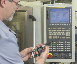 man holding digital caliper in front of CNC