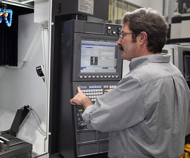 machinist with an Okuma CNC machine