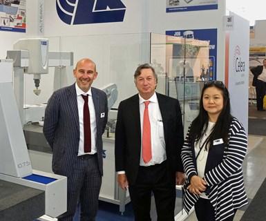 Executives of LK Metrology stand beside machines