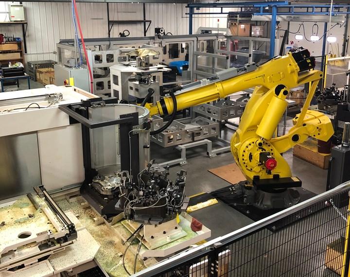 La celda incluye dos tornos verticales, dos máquinas de cinco ejes, un robot grande, racks para materia prima y partes terminadas, y la estación de volteo, que se aprecia aquí, para permitir que el robot agarre el otro lado de la parte.